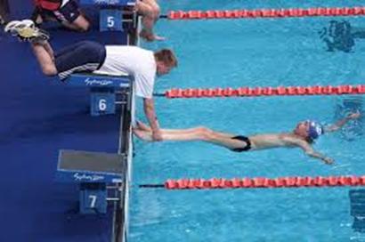 背泳ぎのスタート時に体を支える大会スタッフ